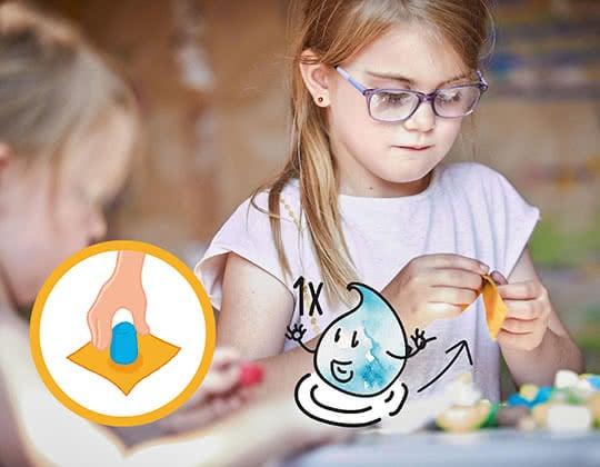 Die Mädchen feuchten das Playmais mit etwas Wasser an